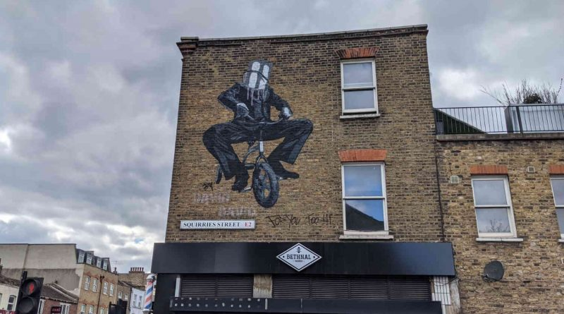 Mural of a man cycling with a paint bucket on his head