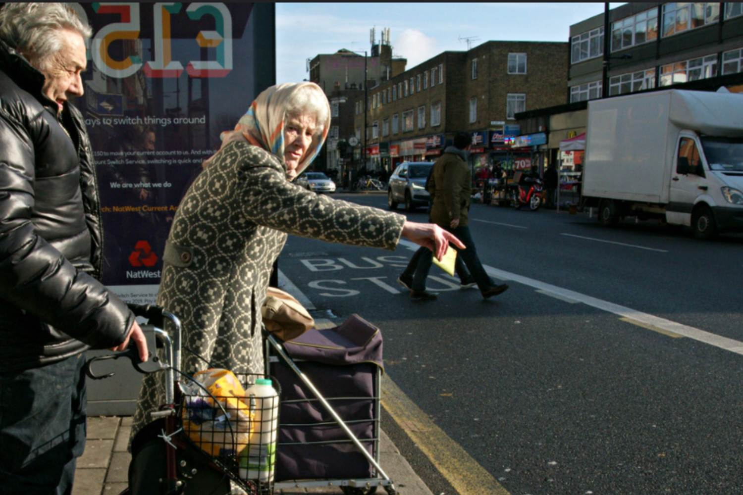 A woman flagging down a bus on Bethnal Green Road