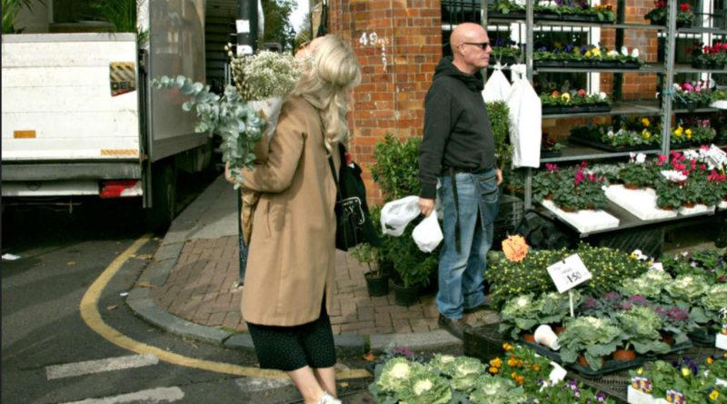 A woman struggling to carry flowers on Columbia Road